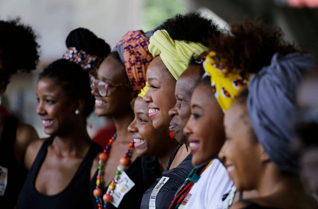 A group of seven African women smile to the side at a camera.