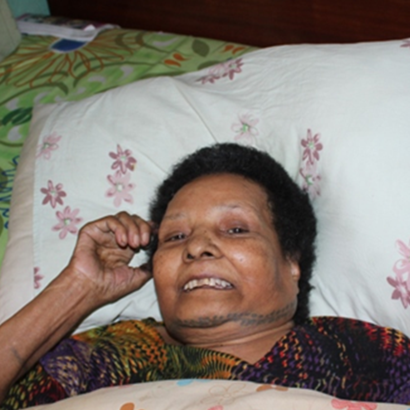 Older woman with short dark hair smiling as lies in bed with floral pillow under her head.