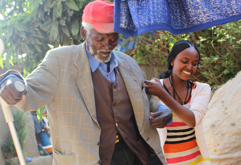 Older man in suit and red cap holding cane, walking with support of aid in striped dress.