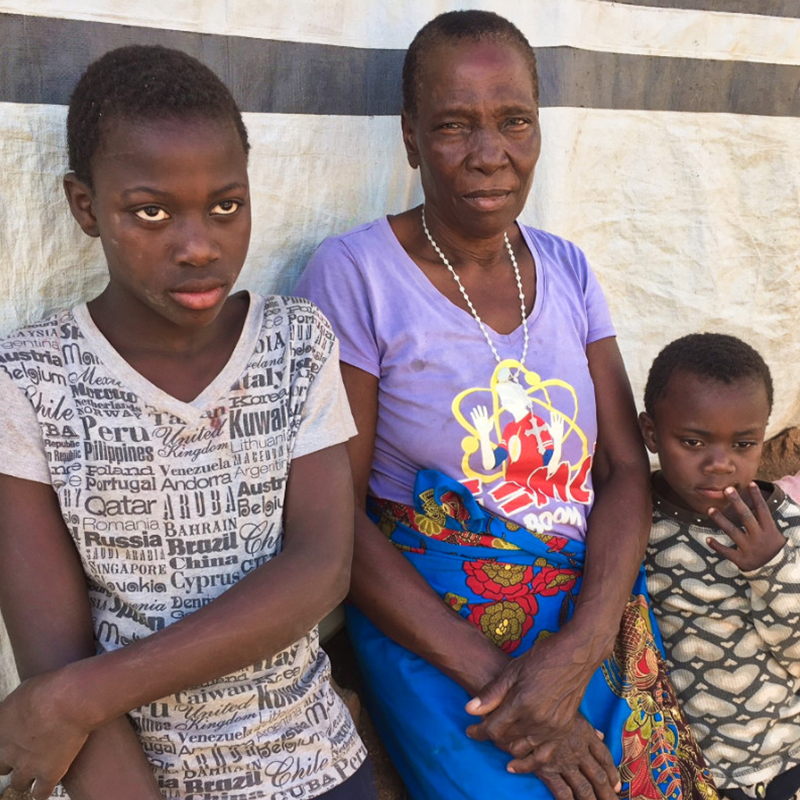 Older African woman in purple and blue outfit with her tall son and smaller younger son.