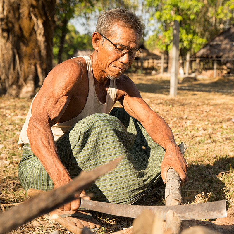Older farmer with muscled arms sitting on ground working with farm instruments.
