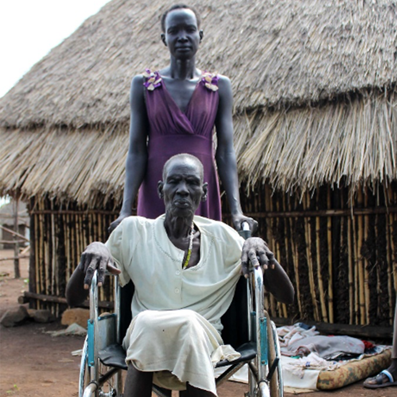 Older woman in white dress sitting in wheelchair with daughter in purple dress behind her, in front of grass shack home.