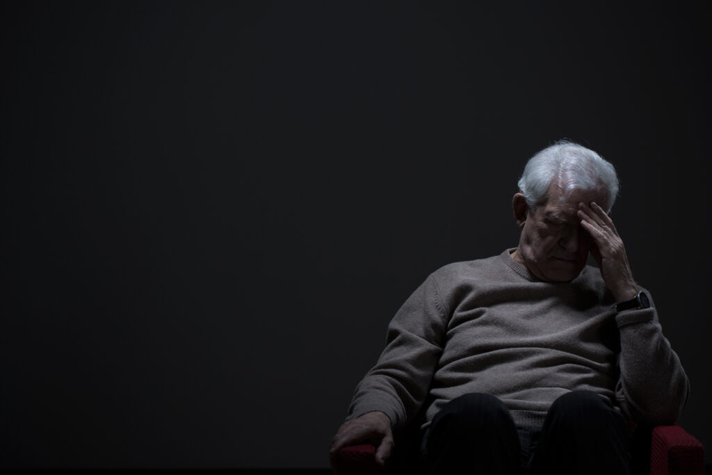 Despairing older man sits with head in his hands
