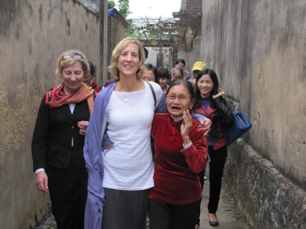 HelpAge USA CEO, Cindy Cox-Roman, smiles with an older woman in Vietnam in an alleyway.