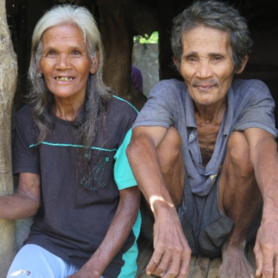 Anita and her son sit beside one another while they smile.
