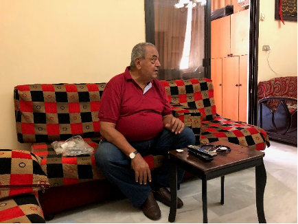 Ibrahim Aoun, an older Lebanese man, sits on a red, black, and brown checkered couch. He wears a red polo shirt as he looks off to the side.