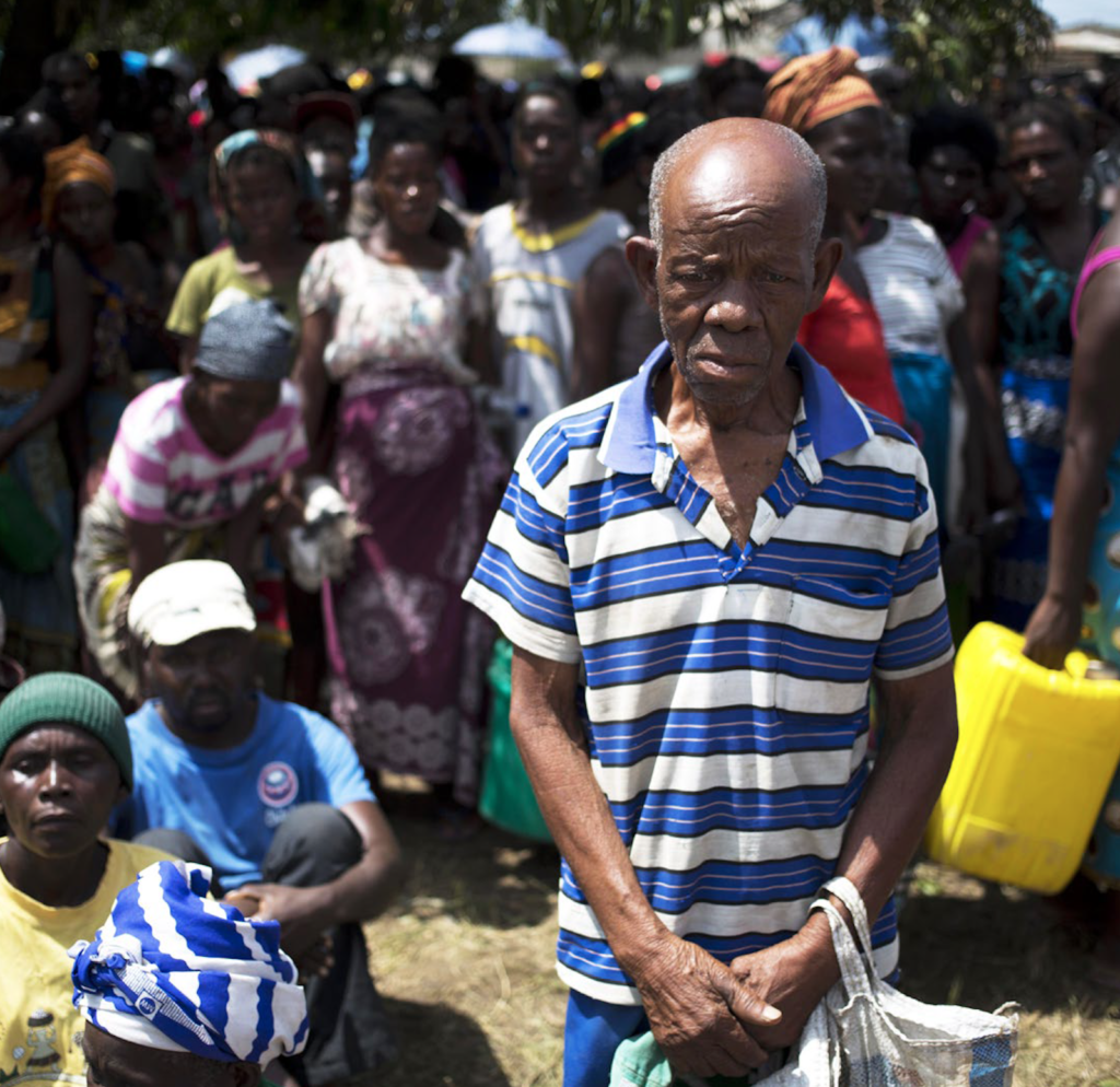 An older African man stares at the ground. He appears distraught. Dozens of people surround him in the background.