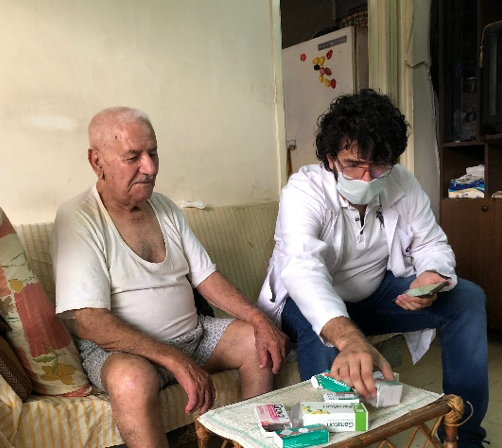 Darwiche Sibliny, an older Lebanese man, sits with his son as they look through health supplies