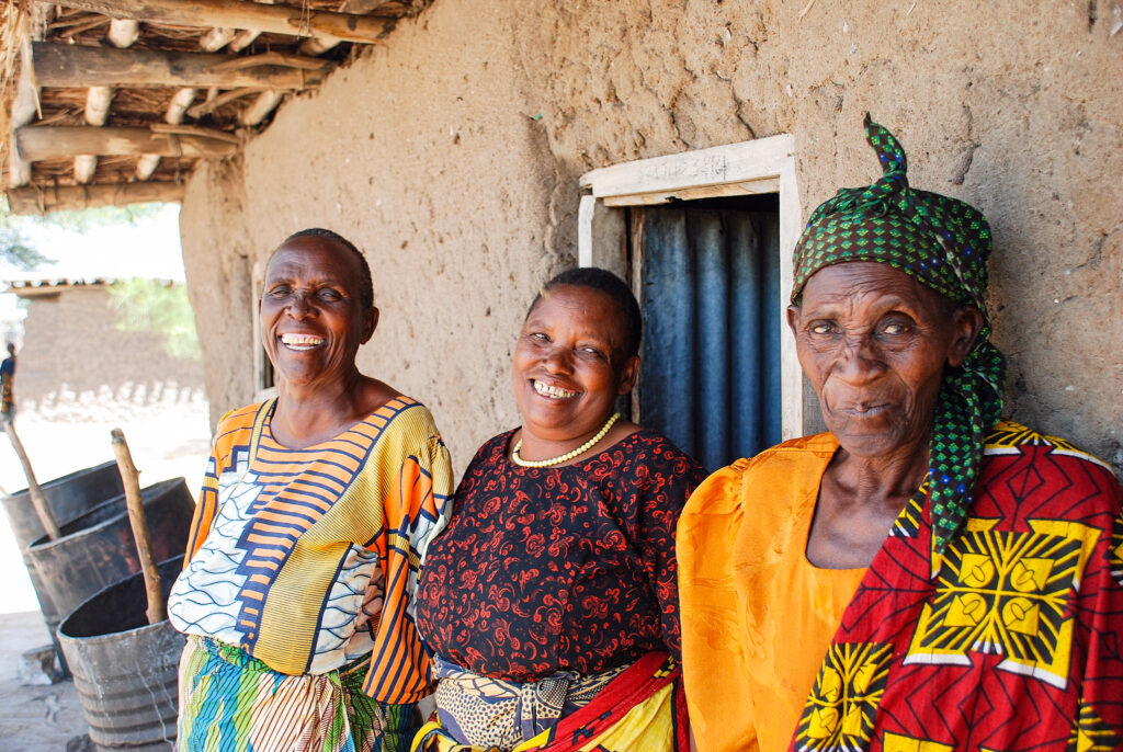 Three African women stand outside a home and smile for the camera