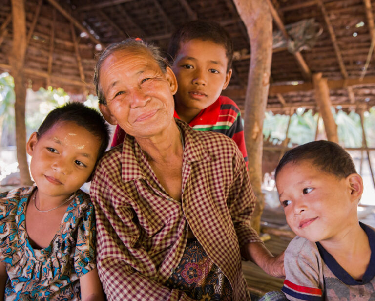 Older Burmese woman smiles with her three grandsons surrounding her