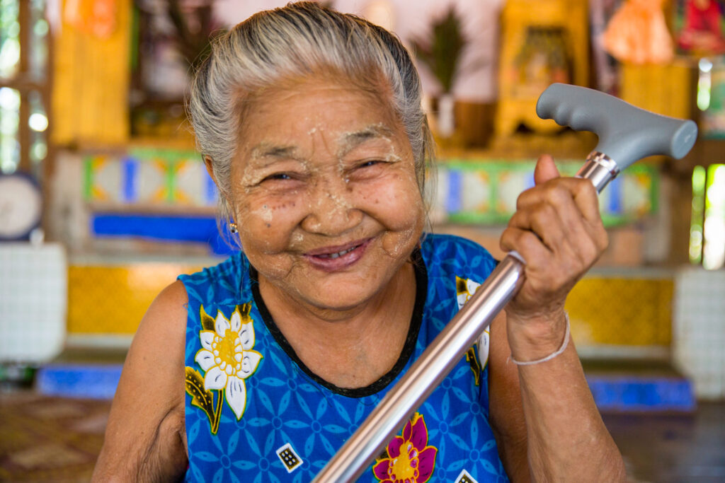 Older woman holds a cane while she smiles
