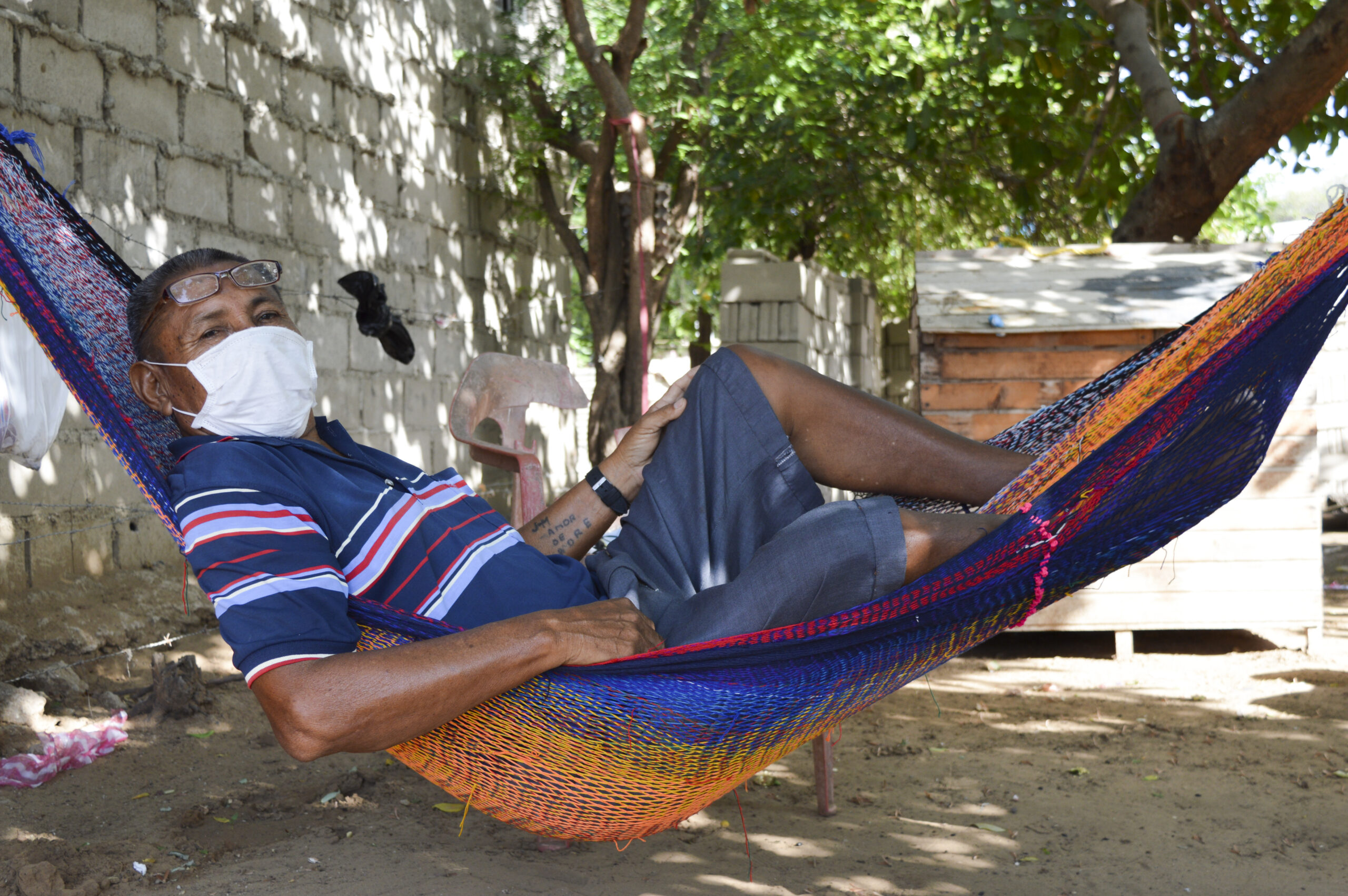 Joaquin lays in a hammock as he wears a white mask.