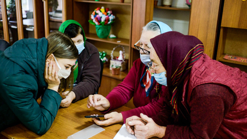 Older and younger Moldovan women use smartphones together at a table.