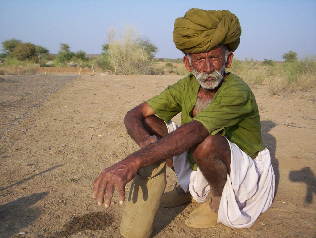 An older man in a green turban and green shirt sits on the ground in India