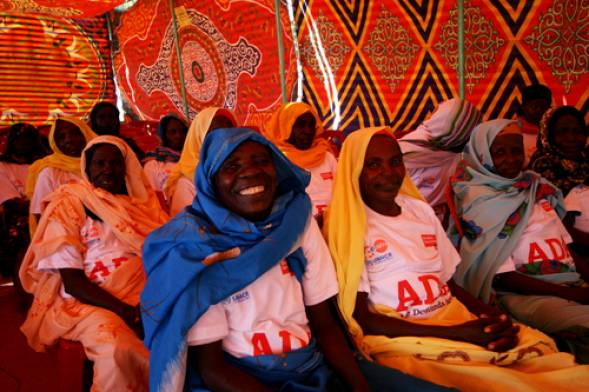 A group of African women in colorful headscarves pose for a photo. They are wearing Age Demands Action shirts.