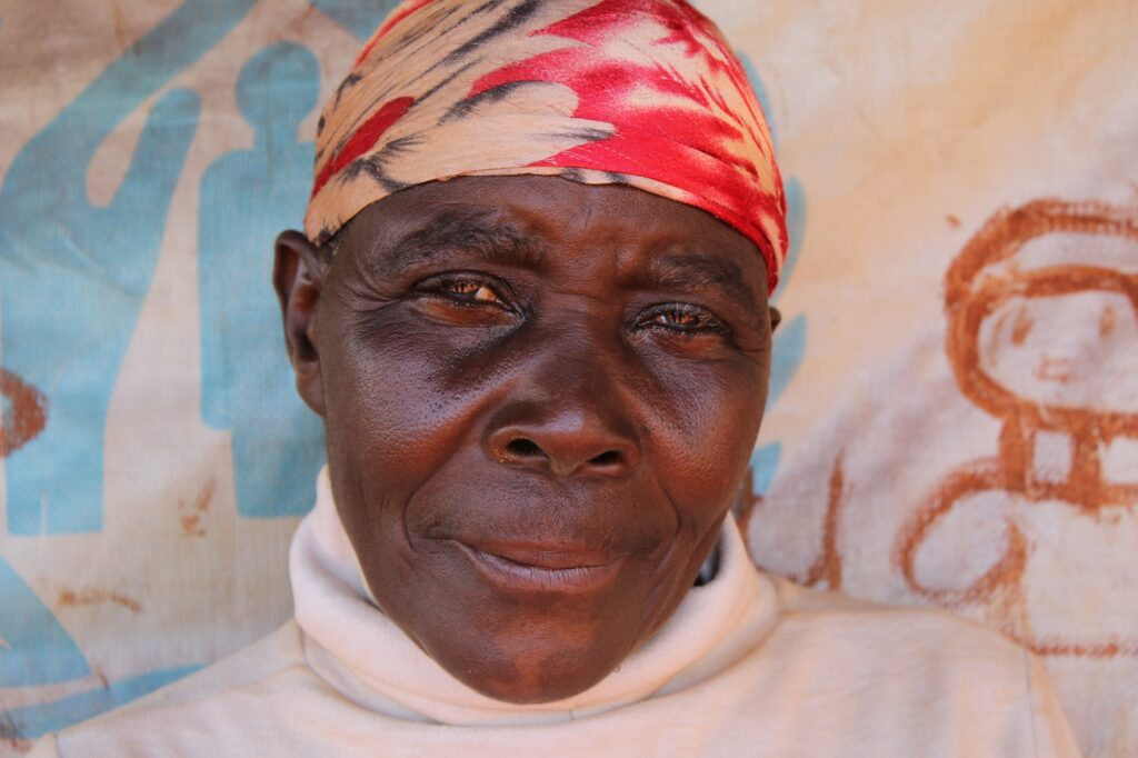Older female African refugee with red and yellow headscarf and white turtleneck shirt