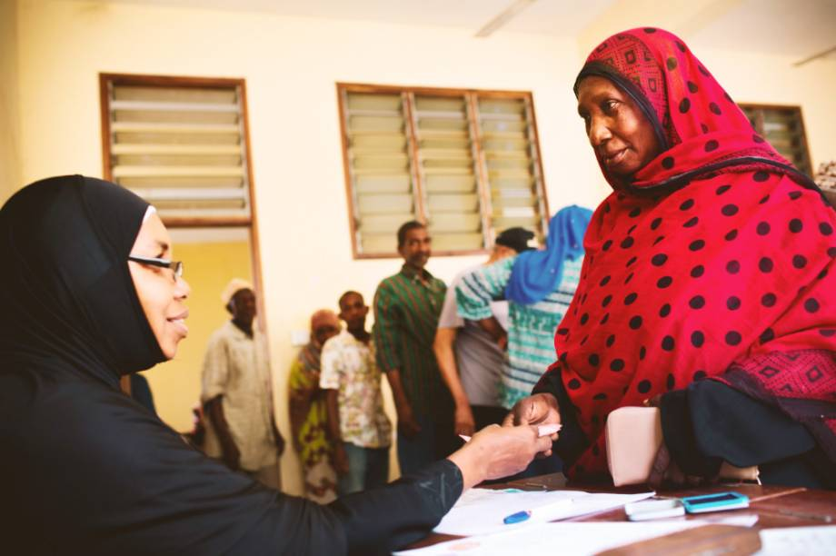 A woman in a black hijab and glasses smiles as she greets a woman in a red and black polka dot hijab. A line forms behind the woman in the red and black polka dot hijab.