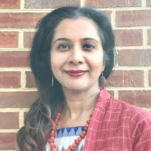 Headshot of Aparna Sanjay standing in front of a brick wall. She is wearing a red checkered blazer, an orange beaded necklace, and a blue blouse.