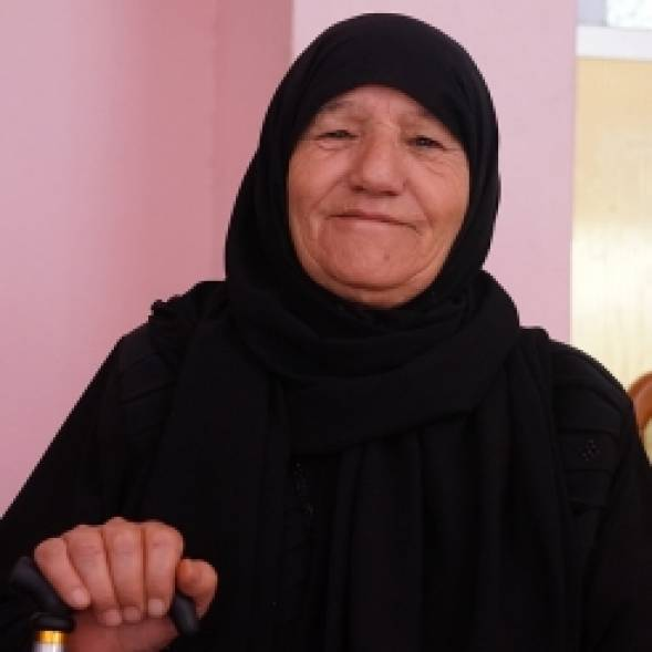 A Jordanian woman in a full black hijab smiles at the camera