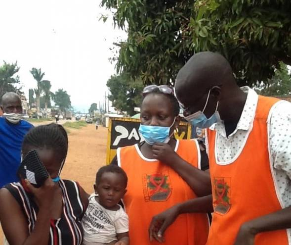 Volunteers for Health Nest Uganda wear masks as they interact with community members.