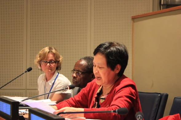 Three women sit as they speak at the UN open-ended working group on aging. An older woman wearing a red jacket speaks into the microphone.
