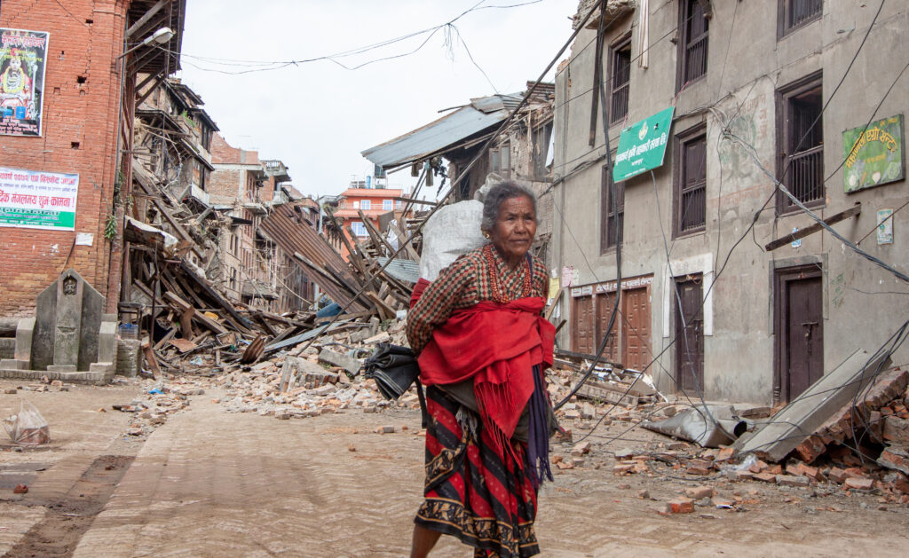 Older woman in Bhakatapur Nepal walks through a destroyed area. She carries a sack on her back and wears a red dress wrapped around her.