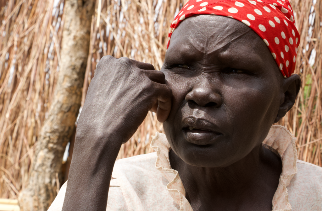 An older African woman looks away in the distance. Her hand is by her face. She wears a red scarf on her head.