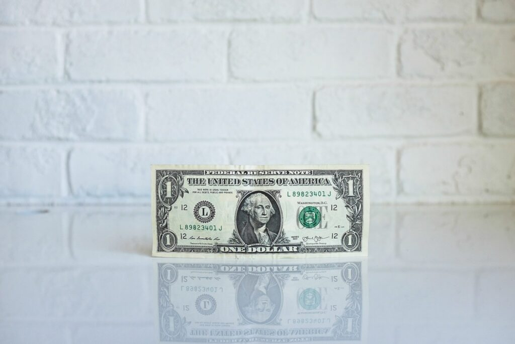 A single dollar bill sits on a reflective table.